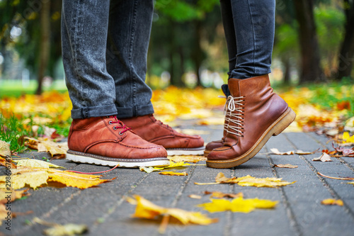Fototapeta  Feet of a couple in love in brown shoes on the path of the autumn park, strewn with fallen leaves