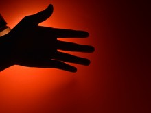 Silhouette Of Hand On Dark Red...