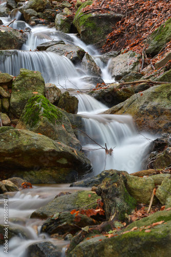 La cascata tra le rocce del bosco in autunno Wall mural