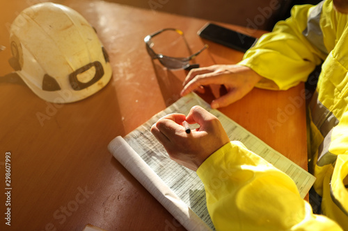 Fototapeta Top view of young construction gold miner worker hand holding pen writing job ha