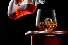 A Glass Of Whiskey And Ice On A Wooden Table In A Low Key. On Top Of The Glass A Man's Hand With A Bottle Of Whiskey.