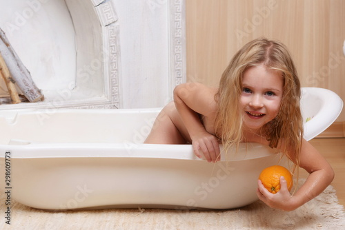 Photo 4 years old girl stretches out of a milk bath for an orange
