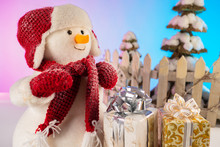 Congratulations To The New Year. Plush Snowman With Gifts. Preparation For Christmas. Greeting Card. Christmas Decor. Packaging Of Christmas Gifts. Toy Snowman With A Red Hat, Scarf And Mittens.