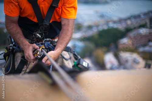 Montage in der Fensternische Lachs Close up pic of male rope access job industrial worker, using a working safety device descender on static twin ropes abseiling, repairing windows at rise building in Sydney city CBD, Australia
