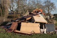 Large-scale, Illegal Fly Tipping Seen In A Rural Location. Showing Household Furniture And Other Home Items Illegally Dumped Overnight.