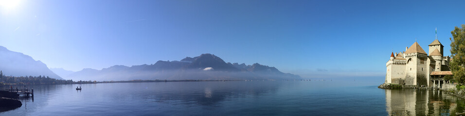 Panoramic view of Chillon castle next to Montreux with fog over the lake in sunny autumn weather