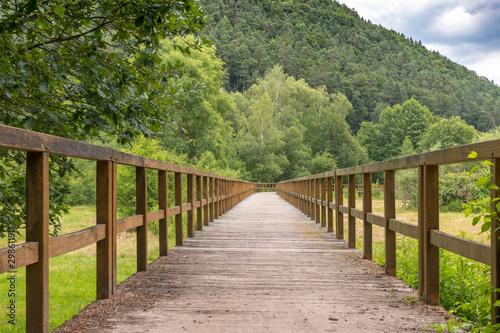 Fototapeta kładka  drewniany-most-nad-polem-z-laka-i-zalesionymi-wzgorzami