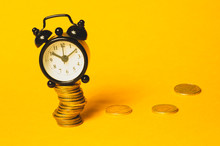 Time Is Money Concept. Classic Alarm Clock With Coins On Yellow Background. Vintage Watch With Round Dial