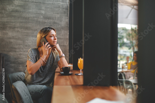 Beautiful young woman drinking coffee and talking on the phone in cafe and looki Wallpaper Mural