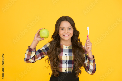 Beautiful natural smile. Happy child hold green apple and toothbrush. Little girl smile with brush and natural fruit. Natural dental care. Gentle natural way to white teeth