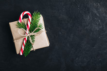 Christmas Gift Box. Christmas Present Box With Candy Cane And Tree Branch On Dark Stone Background.