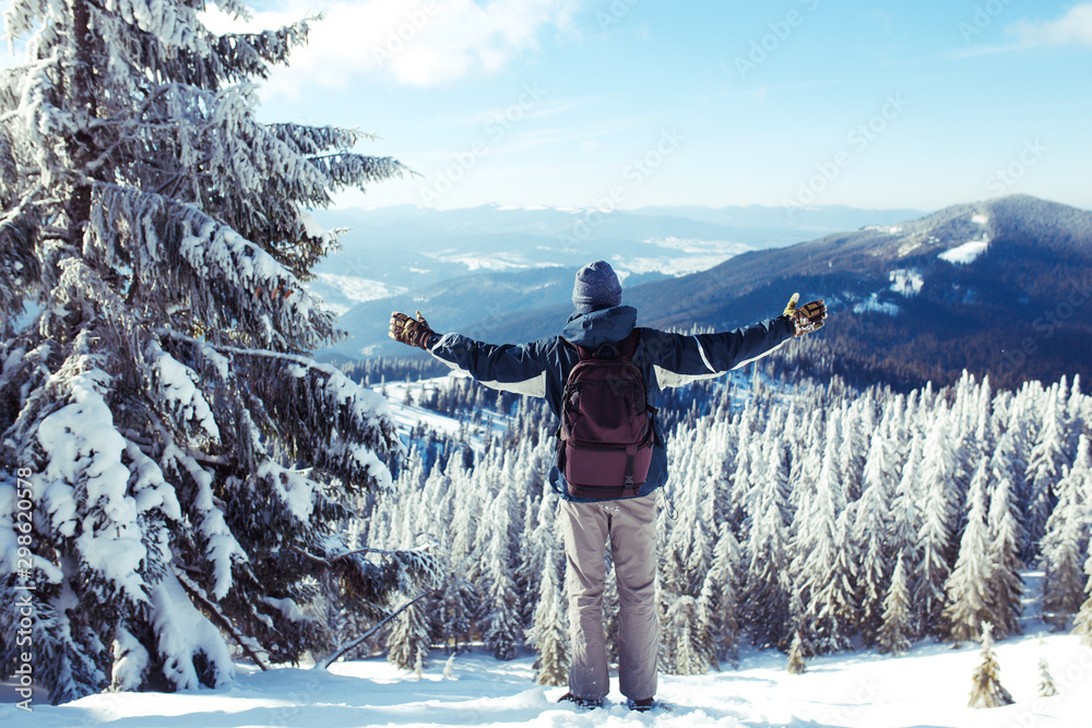 Fototapety, obrazy: Happy man with backpack trekking in mountains. Hiker on the top in  mountains. Cold weather, snow on hills. Winter hiking. Concept of travel, rest, relaxation and sport lifestyle.