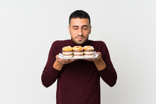 Young Man Over Isolated White Background Holding Mini Cakes Enjoying The Smell Of Them