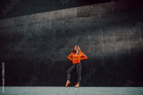 Fotomural  Full length of attractive fit caucasian woman in sportswear posing while standing against black wall