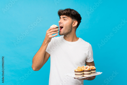 Photo Young handsome man over isolated blue background holding mini cakes and eating i