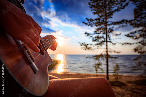 Foto auf Leinwand Braun Woman at sunset holding a ukulele