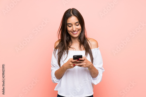 Cuadros en Lienzo  Young woman over isolated pink background sending a message with the mobile