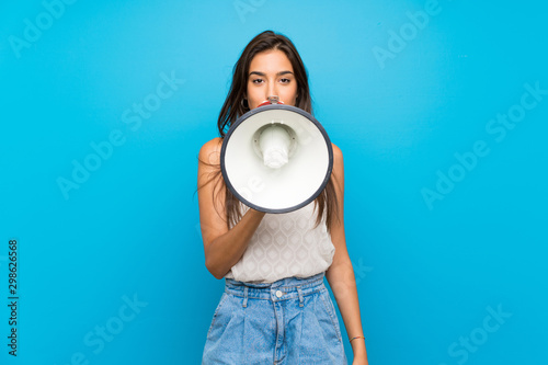 Young woman over isolated blue background shouting through a megaphone Wallpaper Mural