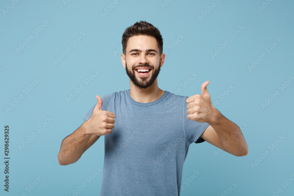Fototapeta Young joyful funny smiling handsome man in casual clothes posing isolated on blue wall background, studio portrait. People sincere emotions lifestyle concept. Mock up copy space. Showing thumbs up. - obraz na płótnie