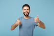 Young joyful funny smiling handsome man in casual clothes posing isolated on blue wall background, studio portrait. People sincere emotions lifestyle concept. Mock up copy space. Showing thumbs up.