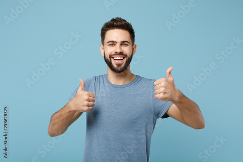Obraz Young joyful funny smiling handsome man in casual clothes posing isolated on blue wall background, studio portrait. People sincere emotions lifestyle concept. Mock up copy space. Showing thumbs up. - fototapety do salonu