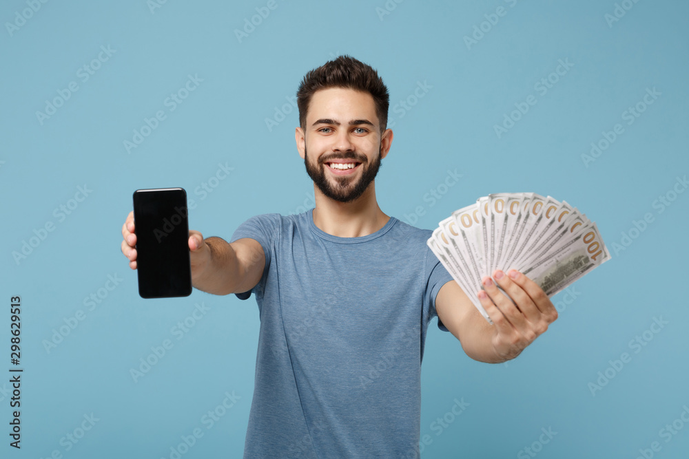 Fototapety, obrazy: Young smiling man in casual clothes posing isolated on blue background. People lifestyle concept. Mock up copy space. Hold mobile phone with blank empty screen, fan of cash money in dollar banknotes.
