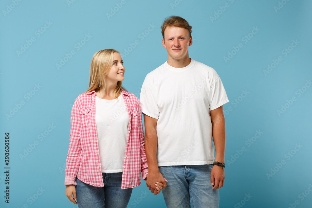 Fototapety, obrazy: Young beautiful couple two friends guy girl in white pink empty blank design t-shirts posing isolated on pastel blue background in studio. People lifestyle concept. Mock up copy space. Holding hands.