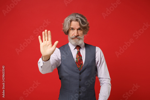 Fotomural  Elderly gray-haired mustache bearded man in classic shirt vest colorful tie isolated on red background, studio portrait