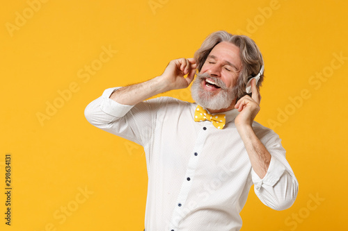 Leinwand Poster  Relaxed elderly gray-haired mustache bearded man in white shirt bow tie isolated on yellow background, studio portrait