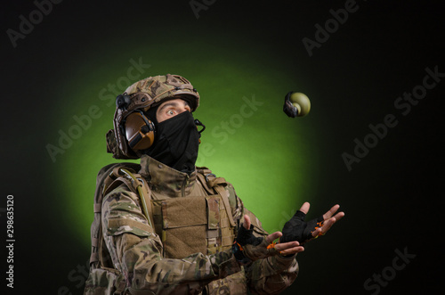 Fotomural  a male soldier in military clothes with a weapon on a dark background