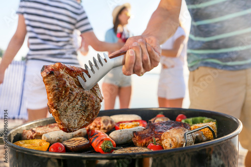 Leinwand Poster Man cooking tasty meat on barbecue grill outdoors, closeup