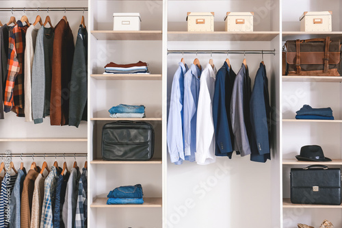 Big wardrobe with clothes in dressing room Fototapet