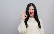 Young Woman With Ok Gesture On A Gray Background