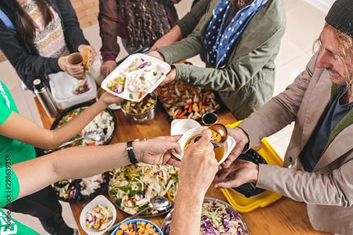 Photo Volunteers giving food to homeless people, top view