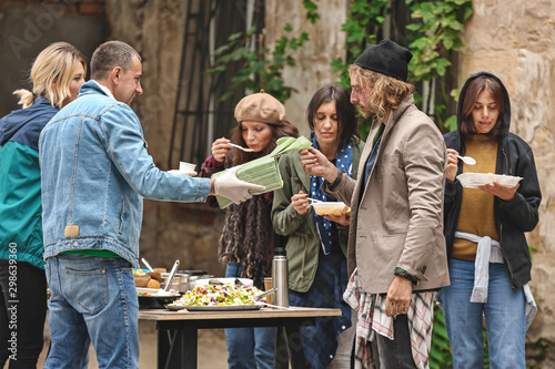 Volunteers giving food to homeless people outdoors Canvas Print