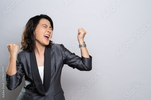 Stampa su Tela  Happy woman make winning gesture isolated over white background