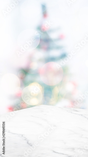 Obraz na plátně  Empty white marble table top with abstract Christmas tree decor string light blur background,Holiday backdrop,Mockup vertical banner for display of product and advertise on online media
