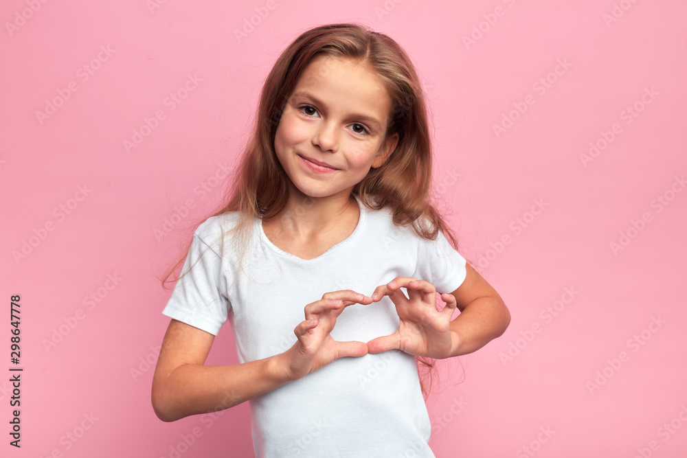 Fototapeta Portrait of young smiling beautiful blonde girl making heart with palms. close up portrait, isolated pink background, body language. reaction, love, positive feeling and emotion