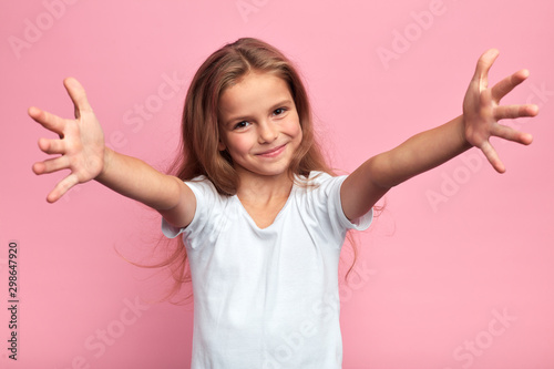 Fototapeta cheerful positive beautiful girl in white t-shirt with arms wide open looking at the camera, kid meeting her guests, welcome, kindness, friendship. close up portrait, isolated pink background obraz