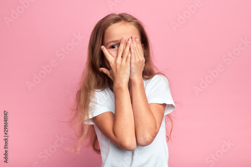 emotional little girl covers her face with her hand isolated over pink background, child watching horror film, movie, reaction, facial expression Canvas Print