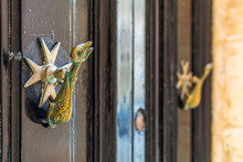 Closeup Of Brass Vintage Knockers As Dolphin With A Trident-shaped Tails And Maltese Cross At Black Wooden Door. Black Door With Cast Brass Hardware With Patina.