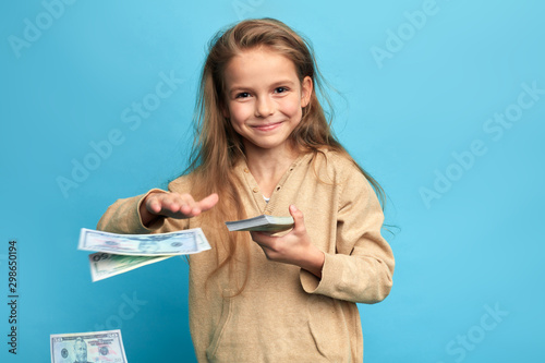 Fotomural cheerful happy girl throwing money, spending money on nothing, useless things, items