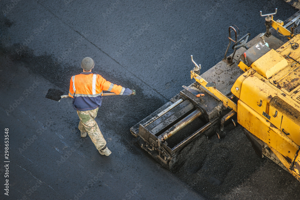 Fototapeta Workers lay a new asphalt coating using hot bitumen. Work of heavy machinery and paver. Top view