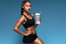 Pleasant Fitness Girl Holding A Bottle And Looking At The Camera, Free Time, Spare Time, Lifestyle. Isolated Blue Background. Studio Shot. Copy Space. Leisure
