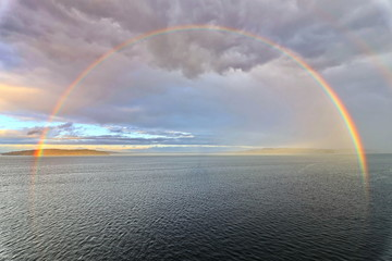 Colorful views of the rainbow against the sky, clouds and sea horizon. Commencement Bay,Tacoma,USA      A.