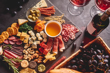 Red Wine With Different Kinds Of Cheese, Charcuterie Assortment, Crackers, Grapes, Nuts And Berries