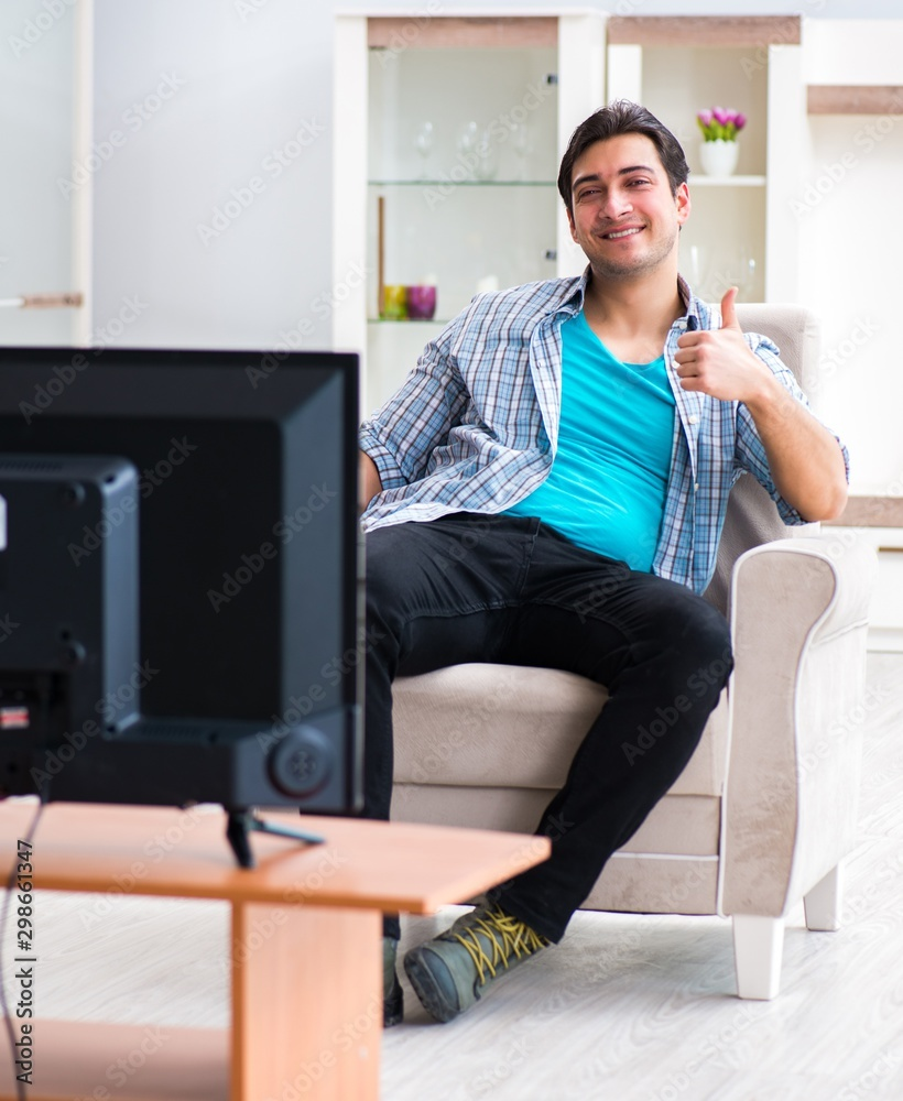 Fototapety, obrazy: Man watching tv at home