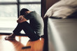 Depressed man. Sad unhappy Man sitting on the floor and holding his forehead while having headache