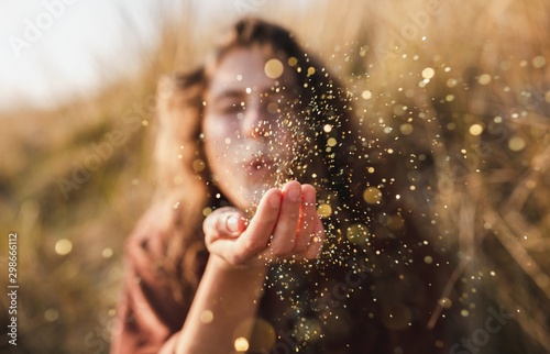Fotografia Beautiful shot of a model blowing glitter from her hand