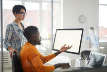 Side View Portrait Of Young African-American Man Looking At Blank Computer Screen And Gesturing While Discussing IT Project With Female Colleague, Copy Space